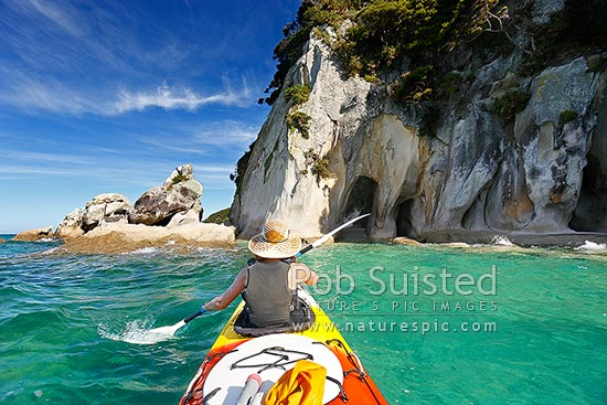 Abel Tasman Coast sea kayaking at the Tonga Arches at Arch Point. Woman kayaker enjoying the summer paddle, Abel Tasman National Park, Tasman District, Tasman Region, New Zealand (NZ) stock photo.
