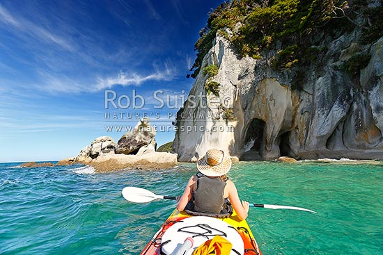 Abel Tasman Coast sea kayaking at the Tonga Arches at Arch Point. Woman kayaker enjoying the summer paddle, Abel Tasman National Park, Tasman District, Tasman Region, New Zealand (NZ).