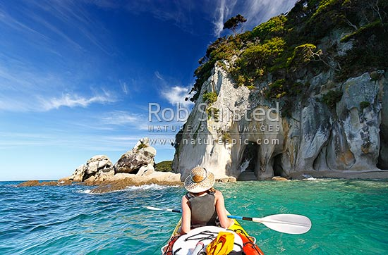 Abel Tasman Coast sea kayaking at the Tonga Arches at Arch Point. Woman kayaker relaxing in summer sun, Abel Tasman National Park, Tasman District, Tasman Region, New Zealand (NZ) stock photo.