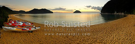 Abel Tasman sunrise at Onetahuti Beach, with Tonga Island and Reef Point (centre) beyond. Tonga Roadstead. Golden sand beach with kayaks. Panorama, Abel Tasman National Park, Tasman District, Tasman Region, New Zealand (NZ) stock photo.