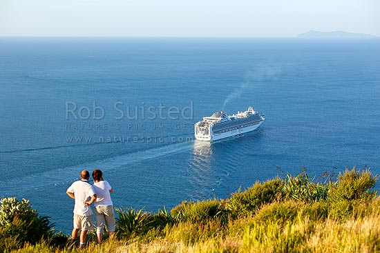 Cruise ship, the Diamond Princess, Princess Cruises departing Tauranga Harbour, viewed by couple watching from summit of Mt Maunganui. Mayor (Tuhua) Island beyond, Mount Maunganui, Tauranga District, Bay of Plenty Region, New Zealand (NZ) stock photo.