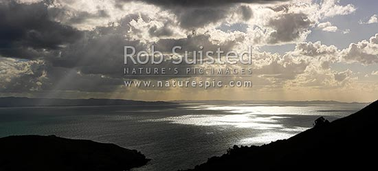 Hauraki Gulf panorama. Moody sunshafts and clouds over sea near Kirita Bay, Coromandel Peninsula, looking towards Auckland, Coromandel, Thames-Coromandel District, Waikato Region, New Zealand (NZ) stock photo.