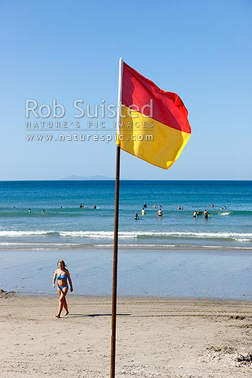 Surf lifesaving safe swimming flag on summertime beach. People swimming in and enjoying surf on holiday, Mount Manganui, Tauranga District, Bay of Plenty Region, New Zealand (NZ) stock photo.