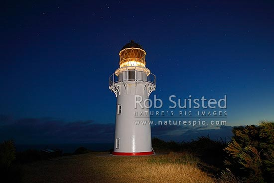 East Cape Lighthouse at dusk and stars above. East Island (Whangoakeno) at left, East Cape, Gisborne District, Gisborne Region, New Zealand (NZ) stock photo.