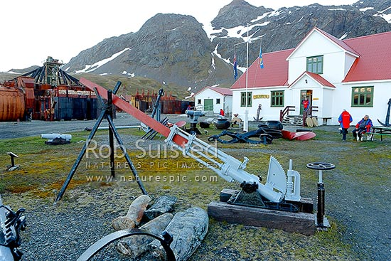 Tourist visitors to historic whaling station museum at Grytviken. Steam driven bone saw in foreground, whaling station at left. Silversea Expeditions, Grytviken, King Edward Cove, South Georgia stock photo.