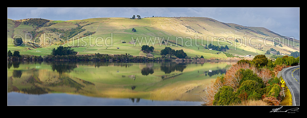 Image of Farmland and rolling pasture reflected in the Catlins Lake. Hinahina Hill. Panorama, Owaka, Clutha District, Otago Region, New Zealand (NZ) stock photo image