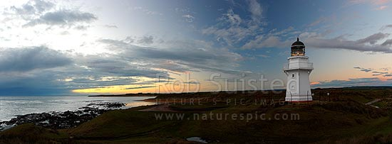 Waipapa Point lighthouse and beach panorama on a moody evening sunset, Fortrose, Southland District, Southland Region, New Zealand (NZ) stock photo.