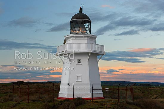 Waipapa Point lighthouse and beach on a moody evening sunset, Fortrose, Southland District, Southland Region, New Zealand (NZ) stock photo.