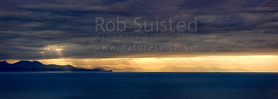 Looking across Cook Strait from Mana Island to the South Island with dramatic sun poking through clouds over entrances to the Marlborough Sounds. Panorama, Mana Island, Porirua City District, Wellington Region, New Zealand (NZ) stock photo.