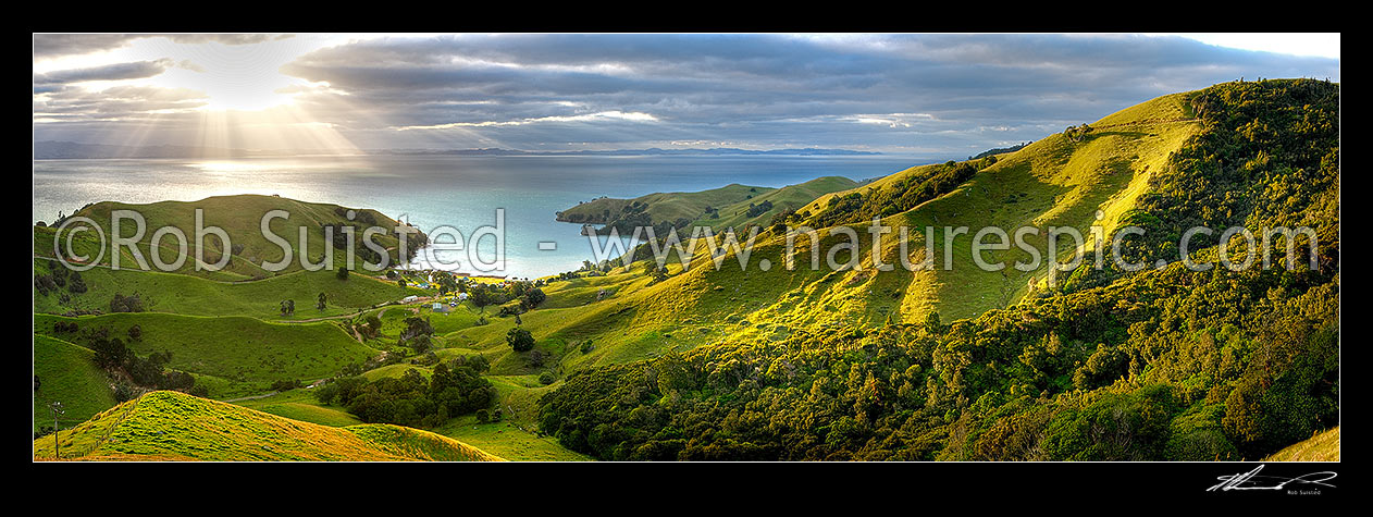 Image of Hauraki Gulf panorama. Moody sunshafts and clouds over sea near Kirita Bay, Coromandel Peninsula, looking towards Auckland. Stunning luch farmland panorama, Coromandel, Thames-Coromandel District, Waikato Region, New Zealand (NZ) stock photo image