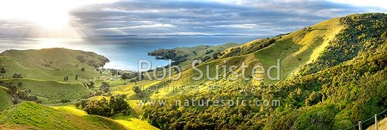 Hauraki Gulf panorama. Moody sunshafts and clouds over sea near Kirita Bay, Coromandel Peninsula, looking towards Auckland. Stunning lush farmland panorama, Coromandel, Thames-Coromandel District, Waikato Region, New Zealand (NZ) stock photo.
