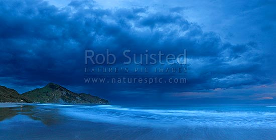 Kaiaua Bay Beach moody twilight panorama, as storm clouds gather, with Marau Point left. Waves breaking on beach blurred in movement, Tolaga Bay, Gisborne District, Gisborne Region, New Zealand (NZ) stock photo.