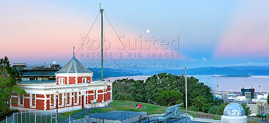 Historic Dominion Observatory built 1907 in Edwardian Baroque style to house the time service. The Krupp gun and Garden Battery to right. Panorama over harbour at dusk with moonrise, Wellington, Wellington City District, Wellington Region, New Zealand (NZ) stock photo.