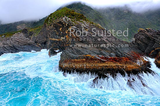 Secretary Island reserve rocky coast with seas breaking. Rugged remote part of the World Heritage Area, Secretary Island, Fiordland National Park, Southland District, Southland Region, New Zealand (NZ) stock photo.