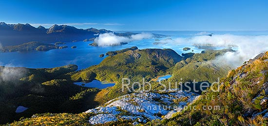 Dusky Sound and Bowen Channel from Resolution Island (Maori: Tau Moana). Indian Is, Cook Channel and Cascade Cove left, Anchor Island right (in cloud). Panorama, Fiordland National Park, Southland District, Southland Region, New Zealand (NZ) stock photo.