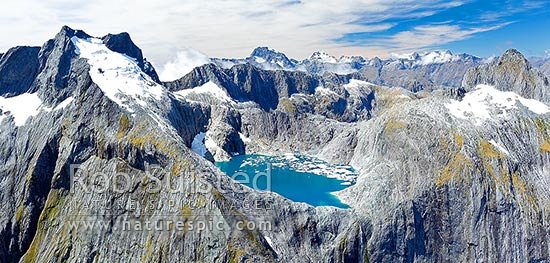 Glacial meltwater lake between Llawrenny Peaks and Terror Peak with icebergs. With Mounts Grave and Tutuko peaks behind. Panorama of shrinking glacier, Fiordland National Park, Southland District, Southland Region, New Zealand (NZ) stock photo.
