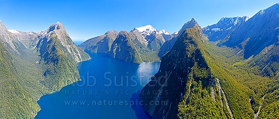 Milford Sound aerial view. Sinbad Gully & Mitre Peak (1683m) left, The Lion, Mt Pembroke and Harrison Cove centre, with Bowen River and Mt Grave right. Piopiotahi. Panorama, Milford Sound, Fiordland National Park, Southland District, Southland Region, New Zealand (NZ) stock photo.