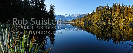 Lake Matheson. Morning calm reflections on lake with Aoraki / Mount Cook (right;3754m) and Mount Tasman (left;3498m). Panorama. South Westland, Westland National Park, Westland District, West Coast Region, New Zealand (NZ) stock photo.