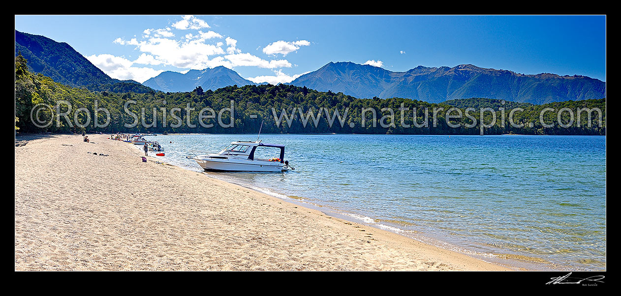 Image of Lake Te Anau at Brod Bay with people enjoying summertime boating and picnics on the beach. Murchison Mountains beyond, Te Anau, Southland District, Southland Region, New Zealand (NZ) stock photo image