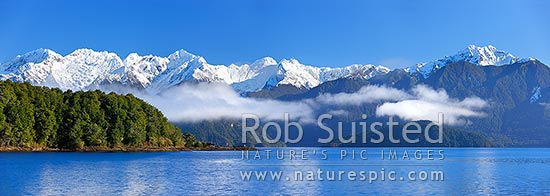 Lake Manapouri morning winter calm with Stony Point bushy headland in front of Kepler Moutains under winter snow. Pomona Island right. Panorama, Te Anau, Fiordland National Park, Southland District, Southland Region, New Zealand (NZ) stock photo.
