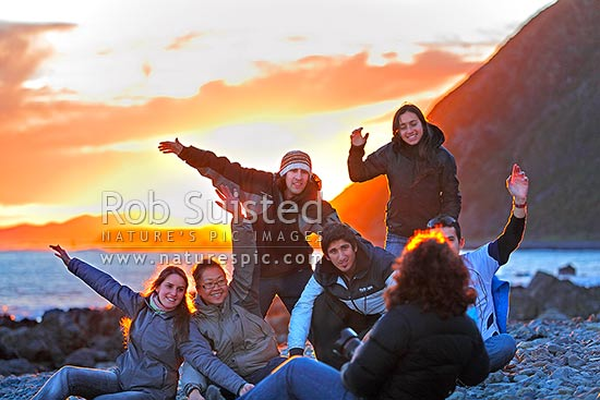 People taking group photograph and enjoying sunset on Wellington South Coast at Sinclair Head, Red Rocks. Travellers, backpackers and tourists, Wellington, Wellington City District, Wellington Region, New Zealand (NZ) stock photo.