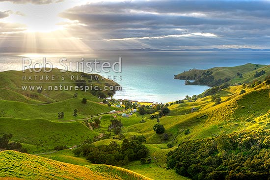 Hauraki Gulf, moody sunshafts and clouds over sea near Kirita Bay, Coromandel Peninsula, looking towards Auckland. Stunning lush farmland, Coromandel, Thames-Coromandel District, Waikato Region, New Zealand (NZ) stock photo.