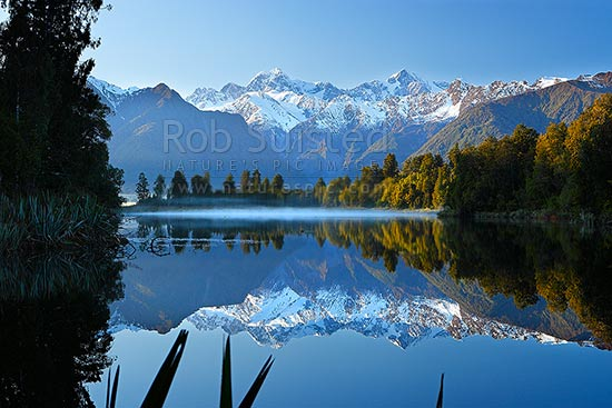 Lake Matheson. Morning calm reflections on lake with Aoraki / Mount Cook (right;3754m) and Mount Tasman (left;3498m). Morning mist, Westland National Park, Westland District, West Coast Region, New Zealand (NZ) stock photo.
