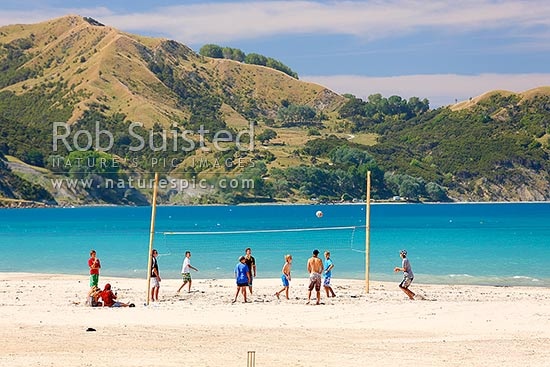 Beach volleyball game on Anaura Bay beach during summer holidays. Young kids and families enjoying the beach, Anaura Bay, East Coast, Gisborne District, Gisborne Region, New Zealand (NZ) stock photo.