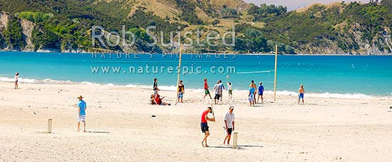 Beach volleyball game and beach cricket match on Anaura Bay beach during summer holidays. Young kids and families enjoying the beach. Panorama, Anaura Bay, East Coast, Gisborne District, Gisborne Region, New Zealand (NZ) stock photo.