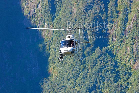 Heliworks Aerospatiale AS350BA Squirrel helicopter being used for aerial HD cineflex filming work in Milford Sound, Fiordland National Park, Southland District, Southland Region, New Zealand (NZ) stock photo.
