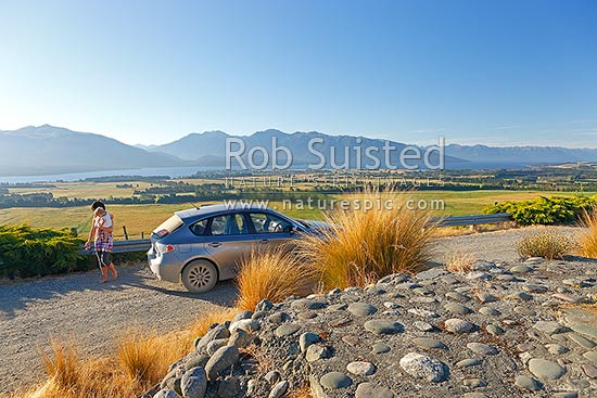 Lake Te Anau, township and Fiordland mountains and national park from lookout with car, and mother and child visitors, Te Anau, Southland District, Southland Region, New Zealand (NZ) stock photo.
