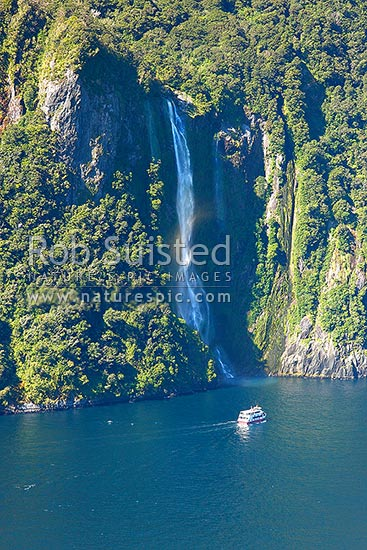 Stirling Falls (146m) spilling from a glaciated hanging valley into Milford Sound. With tour boat below, Milford Sound, Fiordland National Park, Southland District, Southland Region, New Zealand (NZ) stock photo.