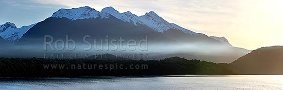 Lake Manapouri at dusk, with snow capped Kepler Mountains behind, in winter. Panorama, Manapouri, Southland District, Southland Region, New Zealand (NZ) stock photo.