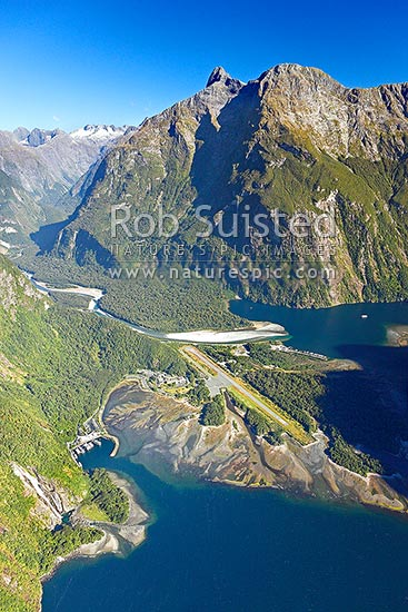 Milford Sound township aerial photo showing Bowen Falls left, Freshwater Basin, Airport, with Cleddau River and Deepwater Basin beyond, and Sheerdown Peak (1878m), Milford Sound, Fiordland National Park, Southland District, Southland Region, New Zealand (NZ) stock photo.