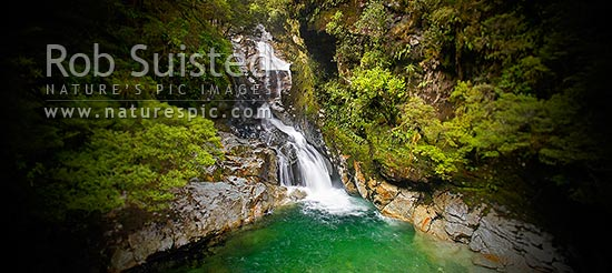 Christie Falls. Falls Creek waterfalls in the Hollyford River Valley, enroute to Milford Sound; panorama with selective focus and vignetting, Fiordland National Park, Southland District, Southland Region, New Zealand (NZ) stock photo.