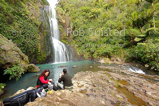 Trampers having lunch and brew at Kitekite waterfall (Kitakita) on Glen Esk stream and the Hillary Trail track near Piha Beach. Waitakere Ranges Regional Park, Waitakere Ranges, Auckland, Waitakere City District, Auckland Region, New Zealand (NZ) stock photo.