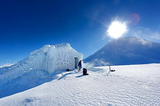 Climber at Syme Hut on Fantham's Peak (Panitahi# at 1962 m, on Mt Taranaki #above), on winter tramping and climbing trip. Hut encrusted with winter ice, Egmont National Park, Taranaki, Stratford District, Taranaki Region, New Zealand (NZ) stock photo.