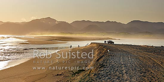 Lake Onoke entrance and Ruamahanga River mouth in Palliser Bay with whitebaiters in evening. Remutaka (Rimutaka) Ranges and Mt Matthews beyond, Lake Ferry, South Wairarapa District, Wellington Region, New Zealand (NZ) stock photo.
