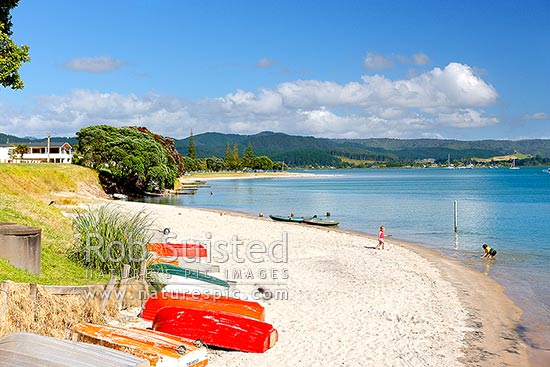 Children playing on beach beside Whangamata Harbour with brightly coloured dinghies on beach, Whangamata, Coromandel Peninsula, Thames-Coromandel District, Waikato Region, New Zealand (NZ) stock photo.