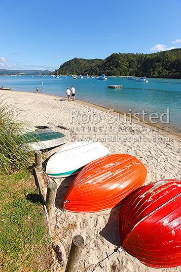 Walkers beside Whangamata Harbour with moored boats and brightly coloured dinghies on beach, Whangamata, Coromandel Peninsula, Thames-Coromandel District, Waikato Region, New Zealand (NZ) stock photo.