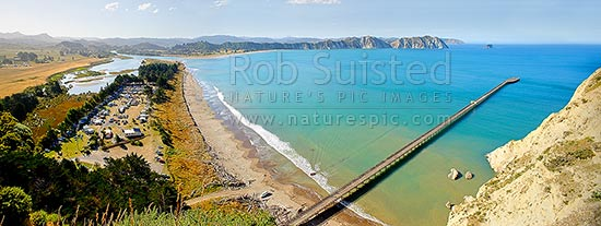 Tolaga Bay wharf in Tolaga Bay. Uawa River mouth and town top left. NZ's longest wharf at 660 metres. Mt Hikurangi distant centre. Panorama, Tolaga Bay, East Coast, Gisborne District, Gisborne Region, New Zealand (NZ) stock photo.