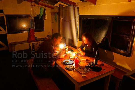Glaisnock Hut with trampers enjoying dinner by candle light, Fiordland National Park, Southland District, Southland Region, New Zealand (NZ) stock photo.