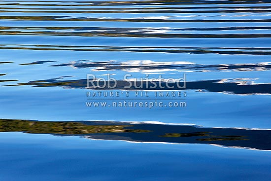 Ripples waves and patterns reflecting on sea water in Fiordland on a calm sunny day, New Zealand (NZ) stock photo.