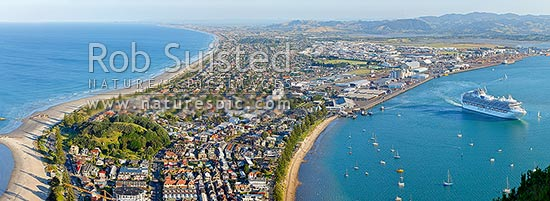 View from Mt Maunganui (232m) over beach and Moturiki and Motuotau Islands, towards Papamoa, Tauranga Harbour right with Diamond Princess cruise ship leaving. Panorama, Mount Maunganui, Tauranga District, Bay of Plenty Region, New Zealand (NZ) stock photo.