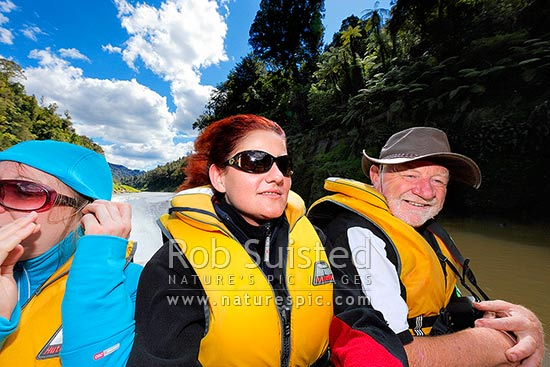 Jet boat riding on the Whanganui River. Tourists and visitors enjoying a popular exciting adventure activity in the National Park, Whanganui National Park, Wanganui District, Manawatu-Wanganui Region, New Zealand (NZ) stock photo.