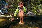 Tramper soaking feet in river