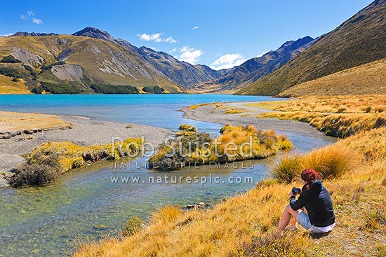 Lake Tennyson Scenic Reserve with visitor taking photos at the head of the Clarence River, inland Marlborough, St James Station, Hurunui District, Canterbury Region, New Zealand (NZ) stock photo.
