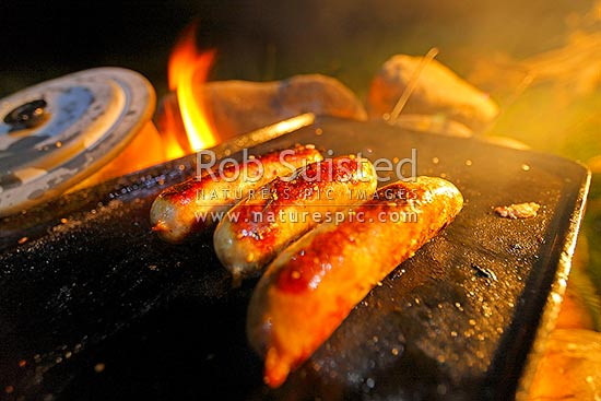 Sausages cooking and barbecuing on open campfire and hotplate at a night time campsite, New Zealand (NZ) stock photo.