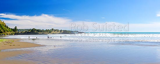 Onepoto Bay and Beach with people and family swimming and bodyboarding in surf. Summertime panorama, Hicks Bay, Gisborne District, Gisborne Region, New Zealand (NZ) stock photo.