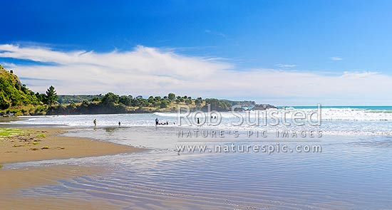Onepoto Bay and Beach with people and family swimming and bodyboarding in surf. Summertime, Hicks Bay, Gisborne District, Gisborne Region, New Zealand (NZ) stock photo.